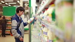 Young man chooses and buys milk at the supermarket. 1920x1080 Stock Footage