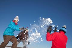 Friends having snowball fight outdoors Kuvituskuvat