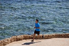Man running on paved coastline Stock Photos