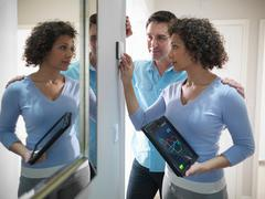 Couple checking thermostat with energy tracking application on digital tablet Stock Photos
