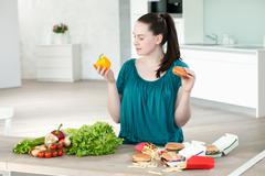 Woman with fast food and vegetables Stock Photos