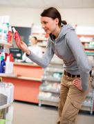 Customer browsing on drugstore shelves Stock Photos