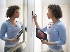 Woman checking thermostat with energy tracking application on digital tablet Stock Photos