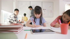 4K Portrait of happy little girl working at her desk in school classroom - stock footage