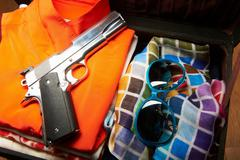 Gun and sunglasses in suitcase - stock photo