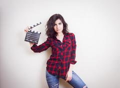 Young woman with movie clapper board on white background - stock photo
