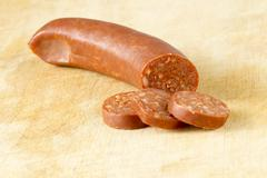 Image of sausage on wooden table - stock photo