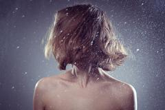 Woman with magnificent hair  in rain and catches drops - stock photo