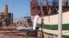 Kyrenia boat harbor - sailor and his cat walk gangplank to sailing ship Stock Footage