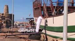 Kyrenia boat harbor - sailor and his cat walk gangplank to sailing ship - stock footage