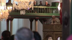 Muslim men enter Islamic mosque while Imam delivers sermon - stock footage