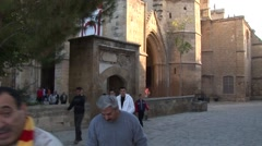 Muslim men leave Islamic mosque, tilt down from and up to minaret Stock Footage