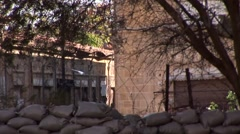 Pan of sandbag bunker protection and wire, main street of Nicosia Stock Footage