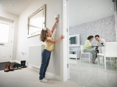 Girl adjusting thermostat in energy efficient house as parents sit in the living Stock Photos