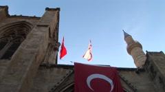 Turkish Cypriot Selimiye Mosque, tilt minarets, flag, to front door Stock Footage
