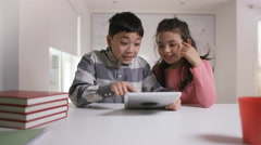 4K Happy little boy & girl working on computer tablet in school classroom Stock Footage