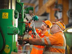 Apprentice engineer and engineer working on drill Stock Photos