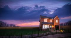 Sunset over landscape and energy efficient house Stock Photos