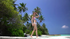 Slender red-haired woman walks along a tropical beach. Slow motion. - stock footage