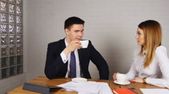 Two happy businesspeople with coffee at office talking - stock footage