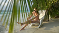Young woman with beautiful legs uses sunscreen on a tropical beach. Slow motion. Stock Footage