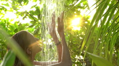 Young slim woman enjoying a refreshing shower in a tropical garden. Slow motion. Stock Footage