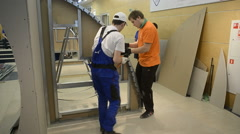Young workers performs task with gypsum cardboard - stock footage