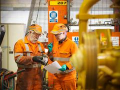 Female apprentice engineer and engineer inspecting gears Stock Photos