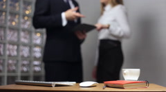Documents on office table and man and woman talking in the background Stock Footage