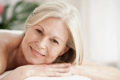Portrait of mature woman on massage table - stock photo