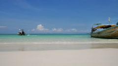 Beautiful traditional long tail tourist boat sails away from the tropical beach Stock Footage