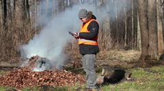 Stock Video Footage of Park Ranger with tablet PC near bonfire