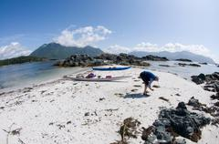 Woman looking for shells on beach, Esperanza Inlet, Vancouver Island, British Stock Photos
