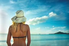Rear view of woman in sunhat looking out to sea Stock Photos