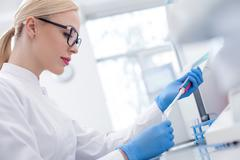 Skillful female laboratory assistant working with flask - stock photo