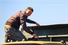smiling young man working on bonnet of tractor - stock photo