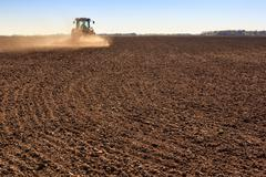 Cultivator operates on ploughed field makes dust Stock Photos