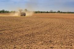 cultivator operates on ploughed field raises dust - stock photo