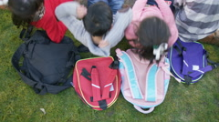 4K Happy group of children lying down on their backpacks on the grass Stock Footage