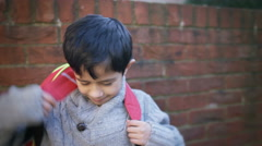 4K Portrait of smiling little boy with backpack, outdoors in school playground Arkistovideo