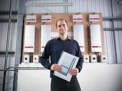 Portrait of worker holding data printout of energy produced from industrial Stock Photos