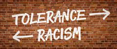 Tolerance or Racism written on a brick wall Stock Photos
