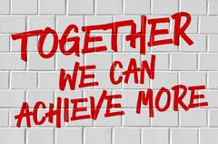 Graffiti on a brick wall - Together we can achieve more - stock photo