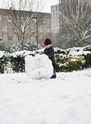 Stock Photo of Boy building snowman in park
