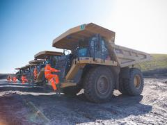 Dumper truck drivers climbing aboard trucks in opencast coalmine Stock Photos