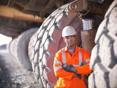 Portrait of miner standing next to  dumper truck tyres in opencast coalmine Stock Photos