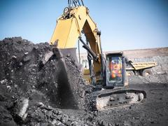 Miner using digger to lift coal from opencast coalmine Stock Photos