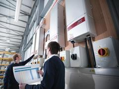 Stock Photo of Two workers inspecting data printout of industrial solar panel controls