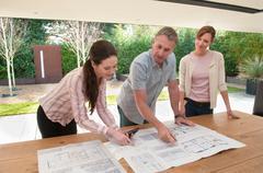 Business people reading blueprints Stock Photos