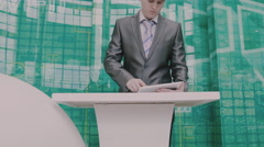 Businessman behind the podium with the tablet - stock footage